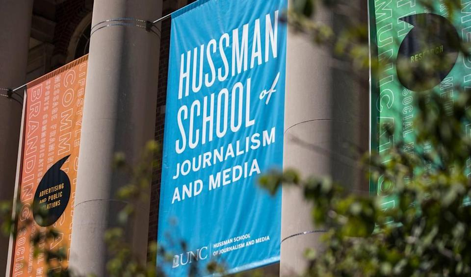 A banner identifying the Hussman School of Journalism and Media at UNC-Chapel Hill hangs above the steps of Carroll Hall in Chapel Hill, N.C., pictured here on Wednesday, July 14, 2021.