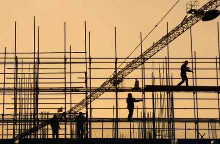 FILE PHOTO: Workers are seen on scaffolding at a construction site in Nantong
