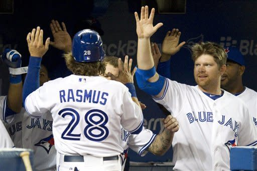 Toronto Blue Jays welcome Colby Rasmus as he returns to the dugout after scoring against the Boston Red Sox during the third inning of a baseball game in Toronto on Monday, April 9, 2012. (AP Photo/The Canadian Press, Frank Gunn)