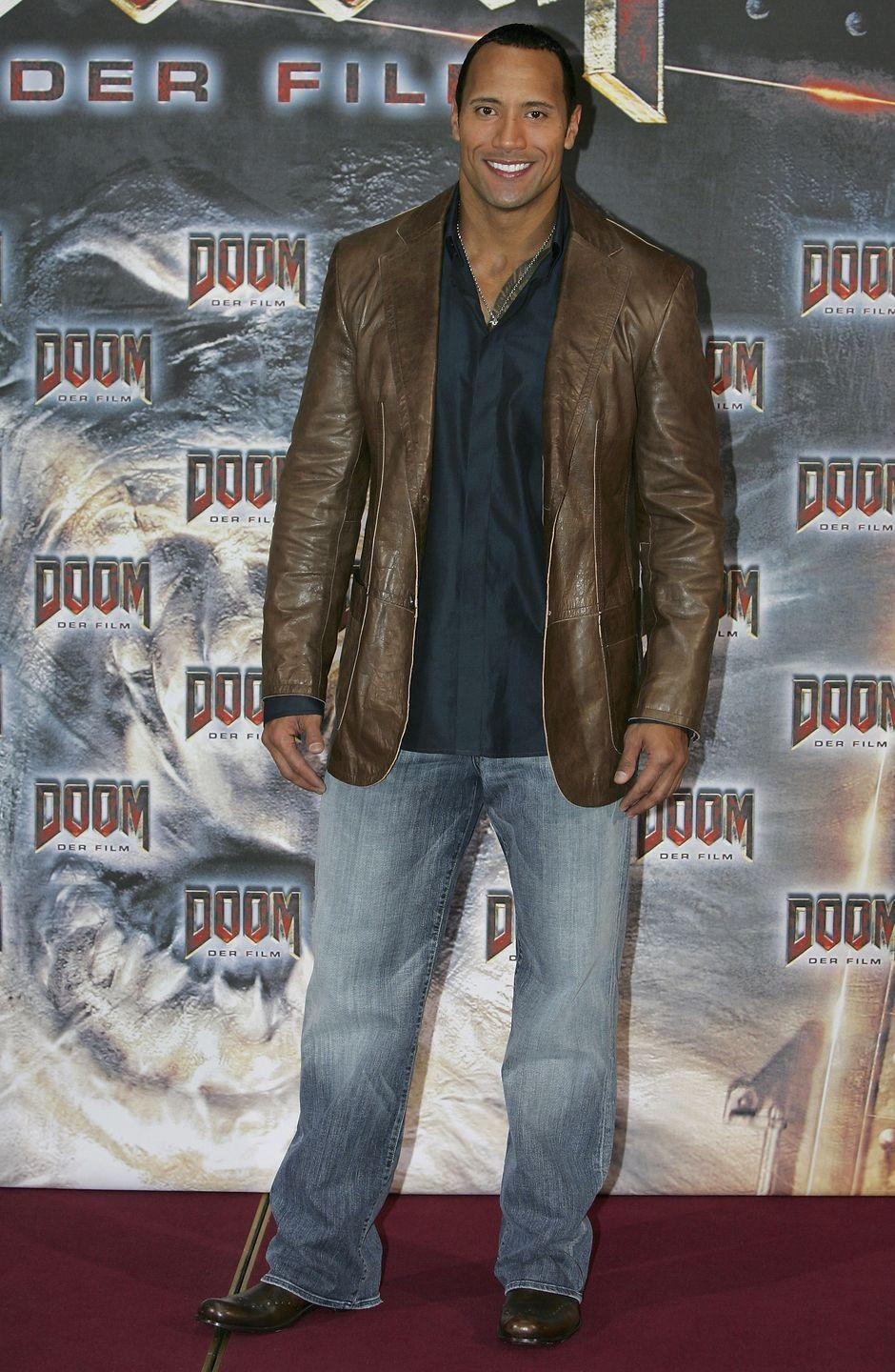 """<p>At a Berlin photocall for the movie <em>Doom</em>, The Rock, ehem, rocked the """"guy waiting in line outside a night club"""" look, including huge jeans, a shiny shirt, a leather jacket, and a silver chain necklace.</p>"""