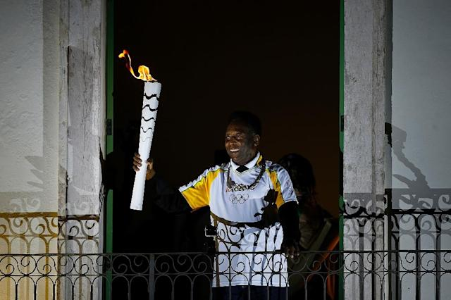 Brazil football legend Pele holds the Olympic flame at the Pele Museum in Santos on July 22, 2016 (AFP Photo/Marcos de Paula)