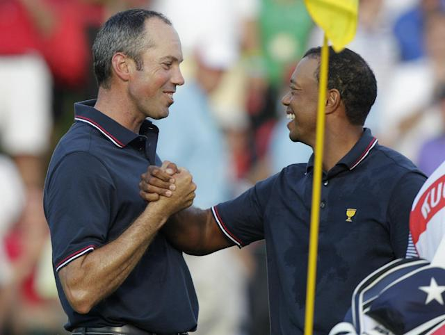 United States' Matt Kuchar, left, and Tiger Woods celebrate their 5 and 4 win over the International team's Angel Cabrera and Marc Leishman in a four-ball match at the Presidents Cup golf tournament at Muirfield Village Golf Club Thursday, Oct. 3, 2013, in Dublin, Ohio. (AP Photo/Jay LaPrete)