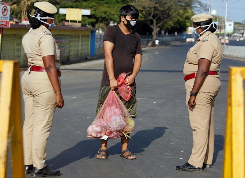 A man carrying vegetables is stopped by police at a barricade on a road on Wednesday in Chennai, India: REUTERS