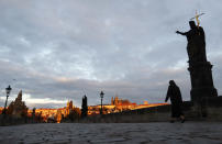 A nun crosses the medieval Charles Bridge as sun rises in Prague, Czech Republic, Thursday, Oct. 8, 2020. Coronavirus infections in the Czech Republic have hit a new record high for the second straight day, surpassing 5,000 cases in one day for the first time. The new confirmed day-to-day increase reached 5,335 on Wednesday, according to Health Ministry figures. It is almost 900 more than the previous record on Tuesday.(AP Photo/Petr David Josek)