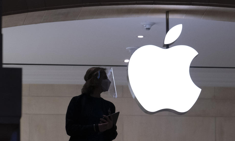 """FILE - In this Feb. 5, 2021, file photo, an Apple store employee wears personal protective equipment in New York. At an event on Monday, June 7, 2021, Apple unveiled a variety of incremental improvements to the software that powers iPhones, iPads and Mac computers"""" would do. (AP Photo/Mark Lennihan, File)"""