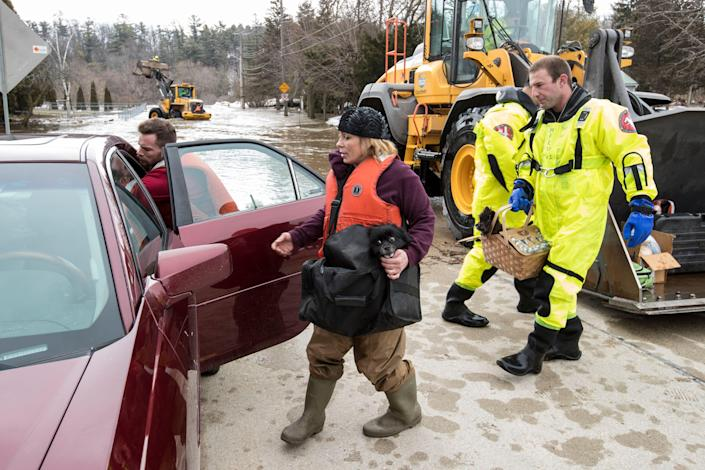 Annette Soukup loads her dog and belongings into her car with help from firefighter Kevin Fabian after being evacuated from her residence due to flooding on the Manitowoc River Thursday, March 21, 2019, in Manitowoc, Wis.