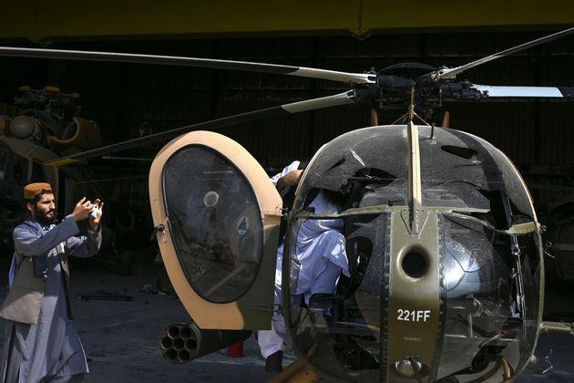 A Taliban fighter (L) takes a picture of a damaged Afghan Air Forces MD 530 helicopter with his mobile phone near the hangar at the airport in Kabul on August 31, 2021, after the US has pulled all its troops out of the country to end a brutal 20-year war -- one that started and ended with the hardline Islamist in power. (Photo by WAKIL KOHSAR / AFP) (Photo by WAKIL KOHSAR/AFP via Getty Images) (Photo: WAKIL KOHSAR via Getty Images)
