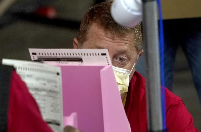 A worker in a red shirt and yellow face mask closely scrutinizes a ballot propped against a pink stand.
