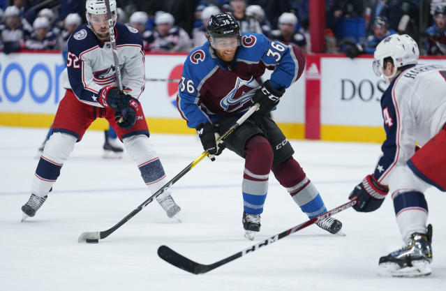 Colorado Avalanche center T.J. Tynan (36) moves the puck between Columbus Blue Jackets center Emil Bemstrom (52) and Scott Harrington (4) during the second period of an NHL hockey game, Saturday, Nov. 9, 2019, in Denver. (AP Photo/Jack Dempsey)
