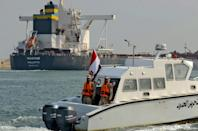 Egyptian coast guards patrol as a ship navigates the newly reopened Suez Canal after a near week-long blockage