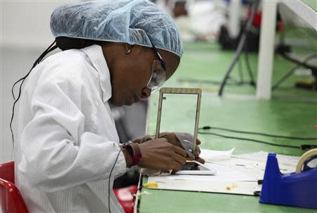 A worker assembles Android-based tablets from imported components at the Surtab factory in the Sonapi Industrial Park of Port-au-Prince March 11, 2014. REUTERS/Marie Arago
