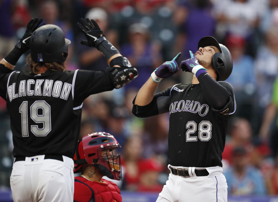 Colorado Rockies' Charlie Blackmon, left, waits to congratulate Nolan Arenado on the latter's two-run home run off St. Louis Cardinals starting pitcher Michael Wacha during the first inning of a baseball game Tuesday, Sept. 10, 2019, in Denver. (AP Photo/David Zalubowski)