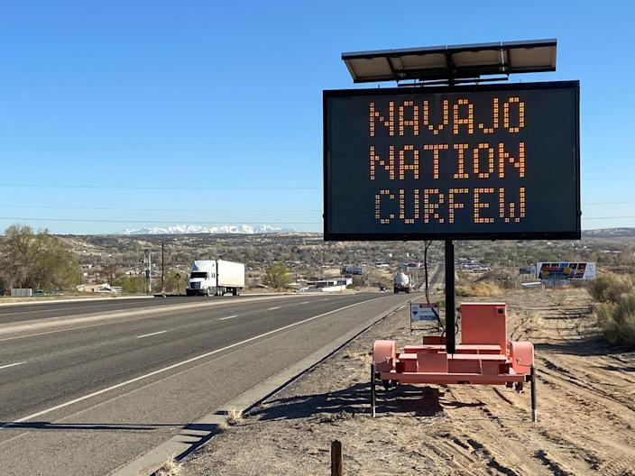 A road sign outside Bloomfield warns Navajos to stay home during their nation's 8pm to 5am curfew to slow the spread of the coronavirus disease (COVID 19), New Mexico, in April 2020.JPG