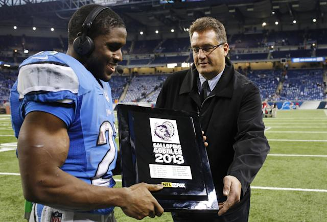 Detroit Lions running back Reggie Bush (21) is presented the Galloping Gobbler award after an NFL football game against the Green Bay Packers in Detroit, Thursday, Nov. 28, 2013. (AP Photo/Rick Osentoski)