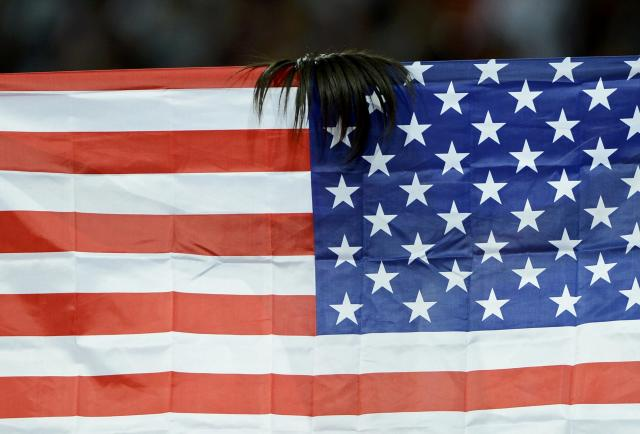 Part of Allyson Felix's hair is seen on top of her national flag, the U.S. flag, as she celebrates winning gold in the women's 200m final during the London 2012 Olympic Games at the Olympic Stadium August 8, 2012. REUTERS/Dylan Martinez (BRITAIN - Tags: OLYMPICS SPORT ATHLETICS TPX IMAGES OF THE DAY)