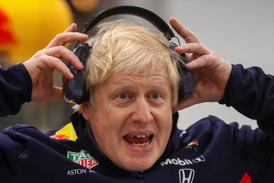 Britain's Prime Minister Boris Johnson adjusts his safety headphones during a visit at Red Bull Racing in Milton Keynes, Britain December 4, 2019. REUTERS/Hannah McKay/Pool