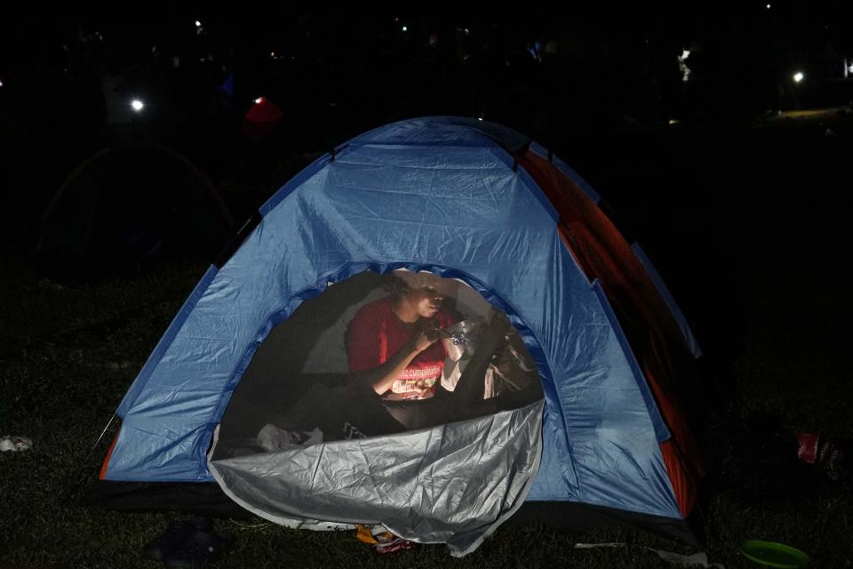 A migrant eats breakfast inside her tent at a camp in Acandi, Colombia, Wednesday, Sept. 15, 2021. The migrants, following a well-beaten, multi-nation journey towards the U.S., will continue their journey through the jungle known as the Darien Gap. (AP Photo/Fernando Vergara)