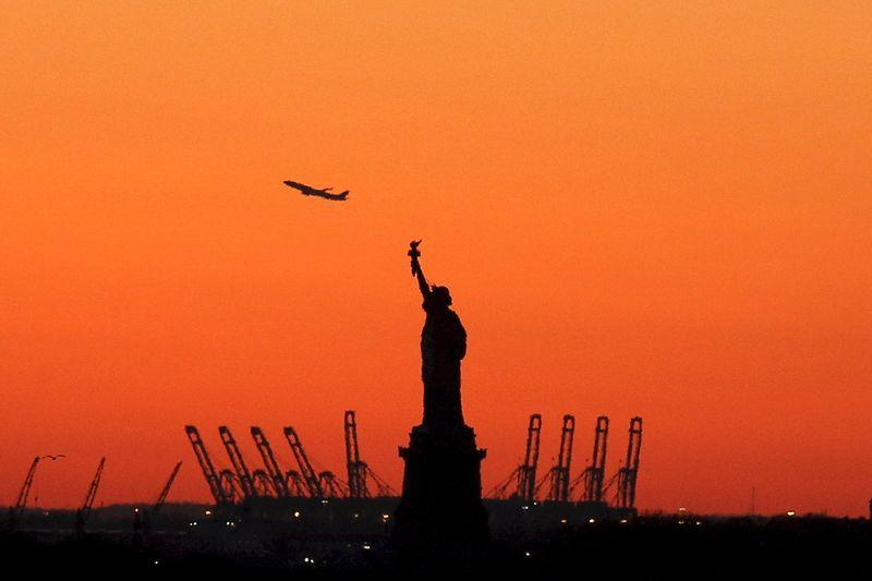A plane is seen during take off behind the Statue of Liberty in New York's Harbor as seen from the Brooklyn borough of New York