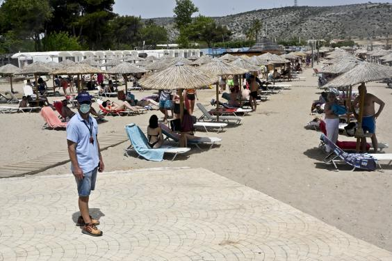 An employee wears a face mask at a beach of Varkiza as Greece gradually eases lockdown restrictions (Getty Images)