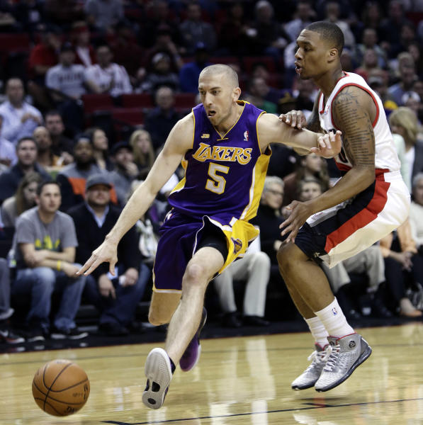 Los Angeles Lakers guard Steve Blake, left, drives on Portland Trail Blazers guard Damian Lillard during the first quarter of an NBA basketball game in Portland, Ore., Wednesday, April 10, 2013. (AP Photo/Don Ryan)