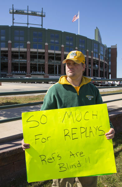 Green Bay Packers fan Mike LePak holds a sign in front of Lambeau Field along Lombardi Avenue, Tuesday, Sept. 25, 2012, in Green Bay, Wis., in protest of a controversial call in the Packers 14-12 loss to the Seattle Seahawks, Monday night in Seattle. Just when it seemed that NFL coaches, players and fans couldn't get any angrier, along came a fiasco that trumped any of the complaints from the weekend. (AP Photo/Mike Roemer)