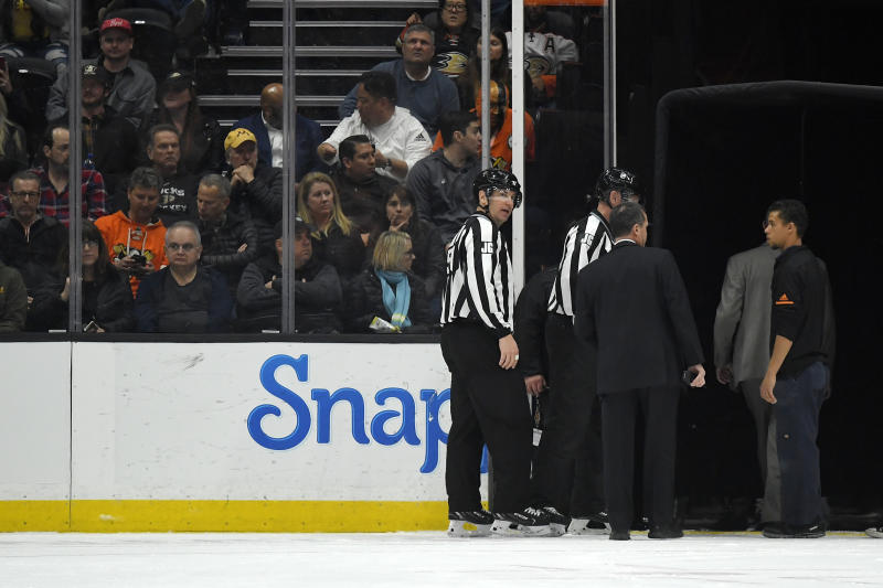 Officials leave the ice after the game between the Anaheim Ducks and the St. Louis Blues was postponed following a medical emergency involving Blues defenseman Jay Bouwmeester during the first period of an NHL hockey game Tuesday, Feb. 11, 2020, in Anaheim, Calif. (AP Photo/Mark J. Terrill)
