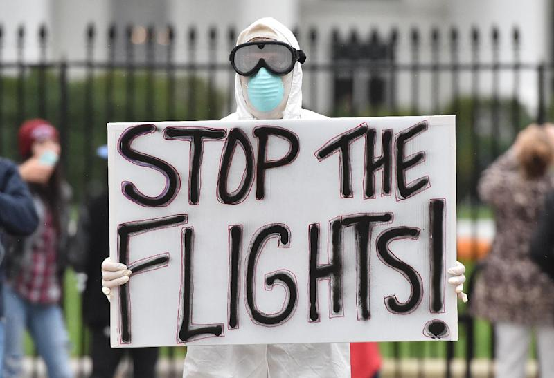 A man dressed in a protective suit and mask holds a poster demanding a halt to all flights from West Africa, as he protests outside the White House in Washington, DC on October 16, 2014 (AFP Photo/Mladen Antonov)