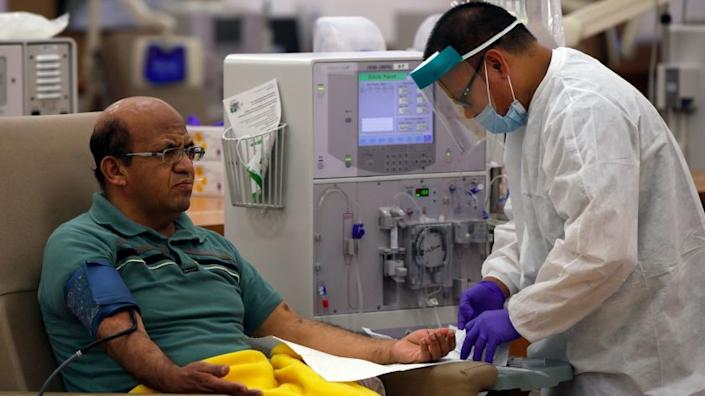 INGLEWOOD, CA. AUGUST 28, 2014 --- Giraldo Garcia, 54, left, waits for dialysis to start as patient care technician Leodegario Ventura, 33, prepares him for the process at DaVita Dialysis Center on August 28, 2014 in Inglewood. (Irfan Khan / Los Angeles Times)