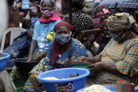 FILE - In this Monday May 4, 2020 file photo, women wearing face masks sell food stuffs at Market in Lagos Nigeria. As coronavirus vaccines trickle into some of the poorest countries in Asia, Africa and the Middle East, data suggest some women are consistently missing out, in another illustration of how the doses are being unevenly distributed around the world. (AP Photo/Sunday Alamba, file)