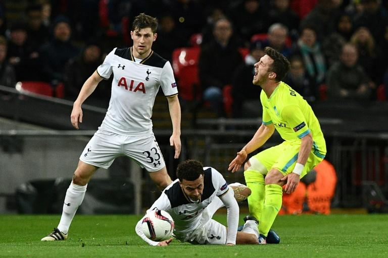 Tottenham midfielder Dele Alli (C) tackles Gent's Brecht Dejaegere earning a red card during the Europa League round of 32 second-leg at Wembley Stadium in north London, on February 23, 2017