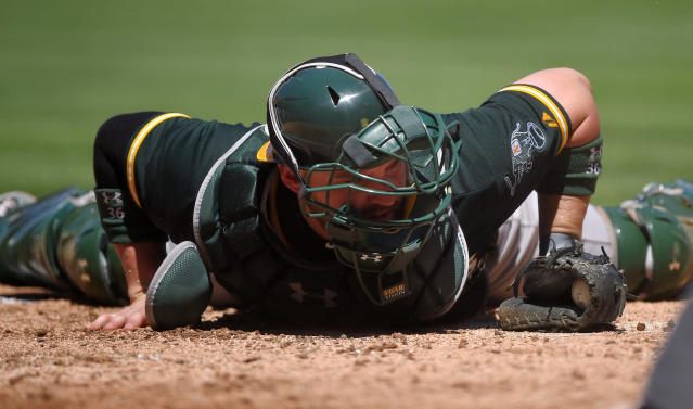 Oakland Athletics catcher Derek Norris lays on the ground after tagging out Los Angeles Angels' Mike Trout as he tried to score on a ball hit by Josh Hamilton during the second inning of a baseball game, Sunday, Aug. 31, 2014, in Anaheim, Calif. (AP Photo/Mark J. Terrill)