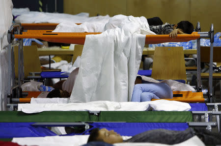 Asylum seekers from various countries sleep as they wait to be registered inside a hall, used by German police as the first registration point, in Passau, Germany July 29, 2015. REUTERS/Michaela Rehle
