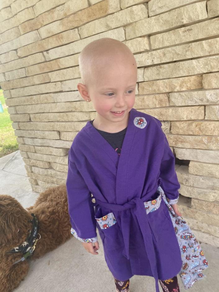 Elliott Hill tries on a superhero robe that she can wear during her hospital stays. / Credit: Handout