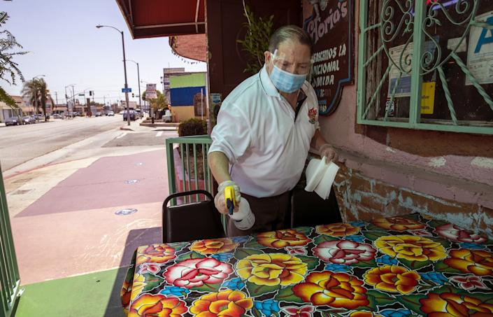 Assistant manager Luis Garcia sanitizes outdoor tables at Gloria's Restaurant in Huntington Park