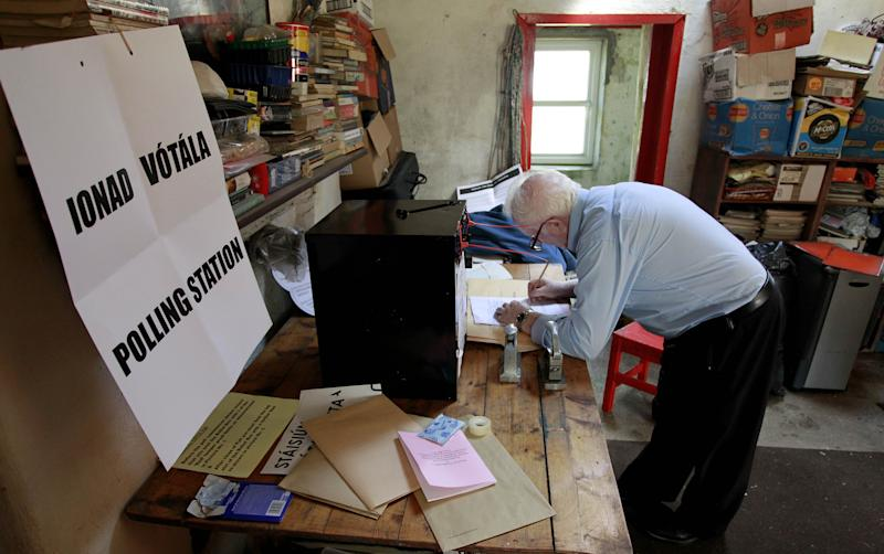 Presiding officer Hugh O' Donnell, right prepares the ballot box on Inishfree Island, county Donegal, Ireland, Monday, May 28, 2012. Barry Edgar Pilcher an artist is the only inhabitant on the island and is using his living room as a polling station to vote in the European Fiscal Treaty Referendum, many island's around Ireland voted Monday ahead of the mainland voting on Thursday.  (AP Photo/Peter Morrison)