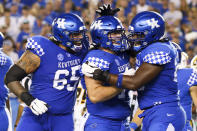 Kentucky offensive tackle Darian Kinnard, guard Eli Cox and guard Kenneth Horsey, from left, celebrate a touchdown during the second half of the team's NCAA college football game against Missouri in Lexington, Ky., Saturday, Sept. 11, 2021. (AP Photo/Michael Clubb)