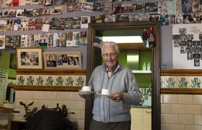 In this photo taken on Thursday, Nov. 7, 2019, Marcel Schmetz serves coffee from the kitchen of his house at the Remember Museum 39-45 in Thimister-Clermont, Belgium. In the bucolic, verdant hills which were once among the worst killing grounds of WWII Marcel and Mathilde Schmetz have shared coffee and cake with countless veterans, telling stories that span generations. Veterans of the WWII Battle of the Bulge are heading back to mark, perhaps the greatest battle in U.S. military history, when 75-years ago Hitler launched a desperate attack deep through the front lines in Belgium and Luxembourg to be thwarted by U.S. forces. (AP Photo/Virginia Mayo)