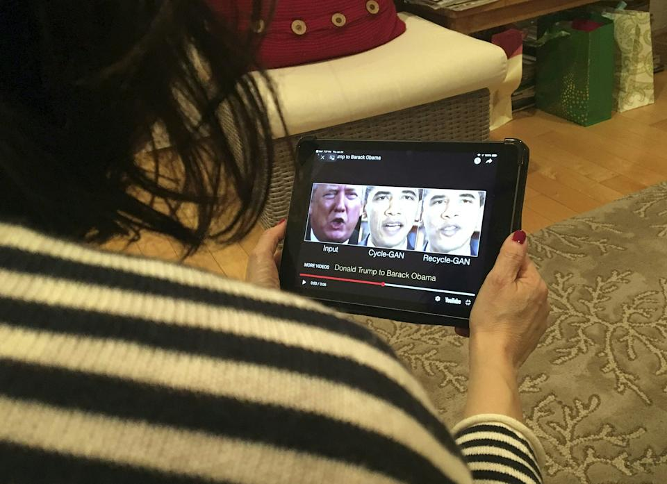 A woman in Washington, DC, views a manipulated video on January 24, 2019, that changes what is said by President Trump and former president Obama, illustrating how deepfake technology can deceive viewers. (Photo by Rob Lever/AFP)
