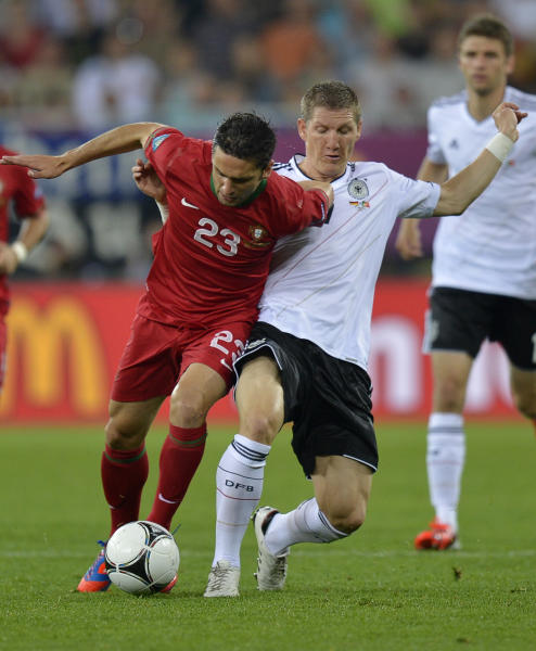 Portugal's Helder Postiga, left, and Germany's Bastian Schweinsteiger fight for the ball during the Euro 2012 soccer championship Group B match between Germany and Portugal in Lviv, Ukraine, Saturday, June 9, 2012. (AP Photo/Martin Meissner)
