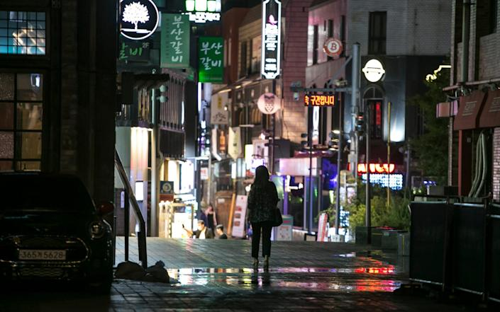 A pedestrian walks through an empty street in the Itaewon district of Seoul - Bloomberg
