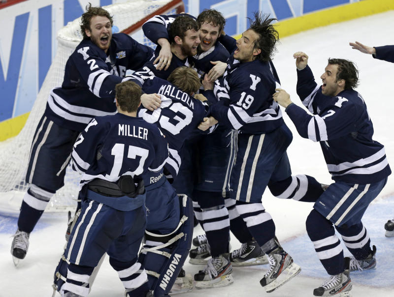 Yale goalie Jeff Malcolm (33) is swarmed by teammates after shutting out Quinnipiac  and leading the Bulldogs to a 4-0 win in the NCAA men's college hockey national championship game in Pittsburgh Saturday, April 13, 2013.  (AP Photo/Gene Puskar)