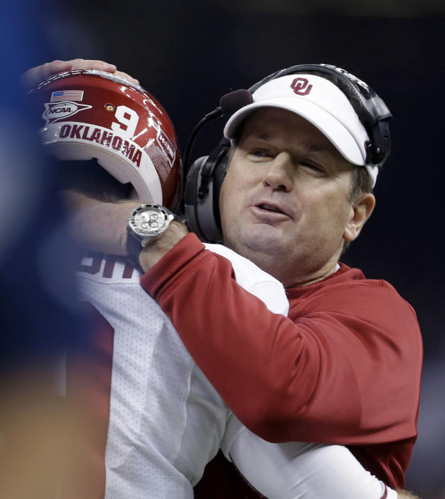 Oklahoma coach Bob Stoops hugs quarterback Trevor Knight during the first half of the Sugar Bowl NCAA college football game against Alabama, Thursday, Jan. 2, 2014, in New Orleans. (AP Photo/Rusty Costanza)