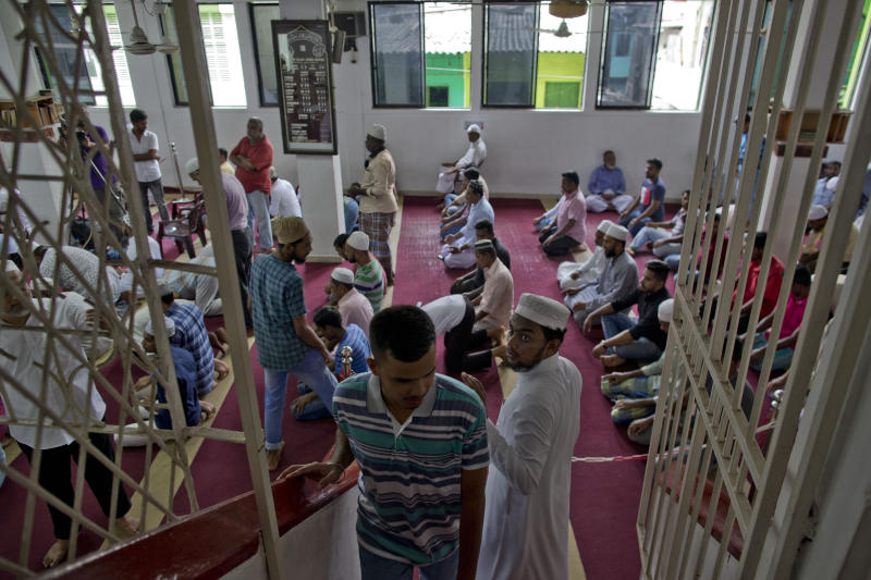 A Muslim volunteer assigned to spot unfamiliar visitors looks at a man ahead of Friday prayers in Colombo, Sri Lanka, Friday, April 26, 2019. Religious leaders cancelled large public gatherings amid warnings of more attacks, along with retaliatory sectarian violence in Sri Lanka though some still held communal Friday prayers at mosques. (AP Photo/Gemunu Amarasinghe)