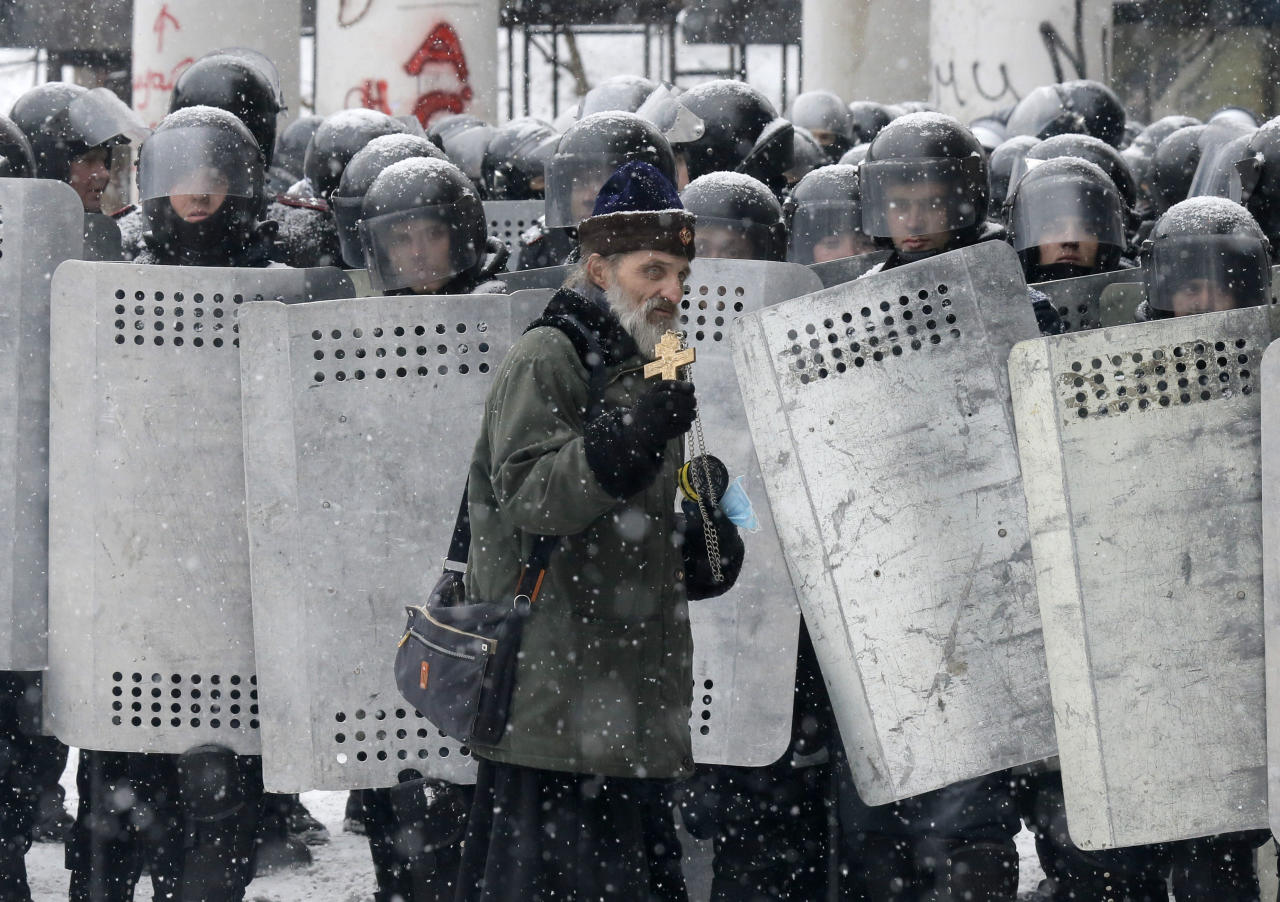An Orthodox priest prays in front of police officers as they block a street after clashes in central Kiev, Ukraine, Wednesday, Jan. 22, 2014. City health officials and police said that two people died of gunshot wounds during the clashes Wednesday morning. But the opposition charges that as many as five people have died. The mass protests in the capital of Kiev erupted after Ukrainian President Viktor Yanukovych spurned a pact with the European Union in favor of close ties with Russia, which offered him a $15 billion bailout. (AP Photo/Efrem Lukatsky)