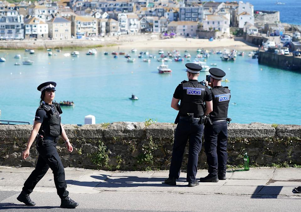 Police officers photograph the route of the motorcade of President Joe Biden after he attended a church service with first lady Jill Biden in St. Ives, Cornwall, England, on June 13, 2021.