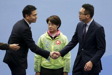 Holden Chow (L), a candidate from the Democratic Alliance for the Betterment and Progress of Hong Kong, congratulates Alvin Yeung (R), a candidate from Civic Party, after Yeung won a Legislative Council by-election in Hong Kong, China February 29, 2016. In the middle is independent candidate Christine Fong.  REUTERS/Bobby Yip