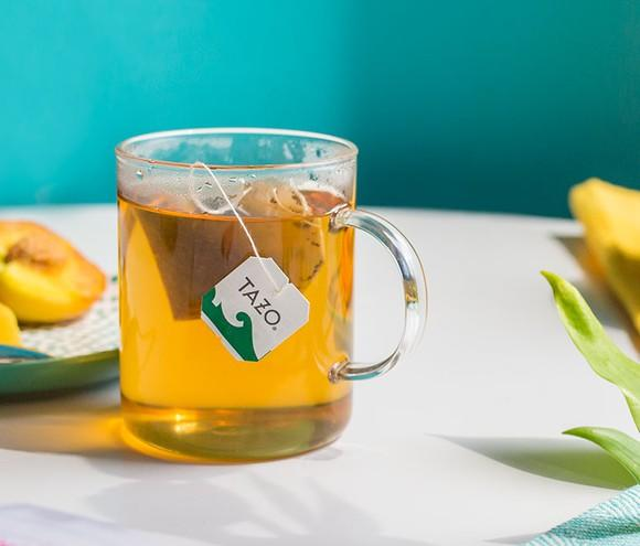 A cup of Tazo tea in a clear glass, sitting on a tablerop near flowers and a plate of fruit.
