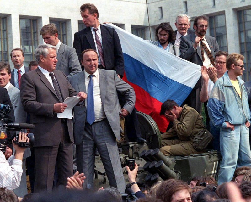 FILE - Boris Yeltsin, president of Russian Federation, left, reads a statement from atop a tank in Moscow in this  Aug. 19, 1991 file photo, as he urges the Russian people to resist a hardline takeover of the central government. Those who were by Yeltsin's side describe his decision to climb onto the tank as a stroke of political brilliance that proved crucial for the defeat of the coup. Among those with Yeltsin was his top adviser Gennady Burbulis, who recently spoke to The Associated Press about those days 20 years ago. (AP Photo/File)