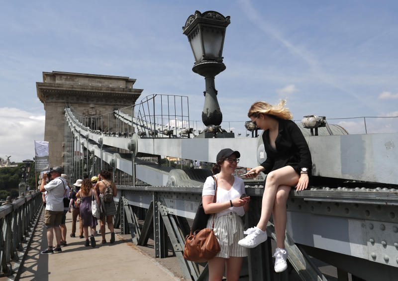 In this photo taken on Wednesday, June 5, 2019, tourists and Hungarians walk on the Chain Bridge over the Danube River in Budapest. A tourism boom in the Hungarian capital has led to major congestion on the river flowing through the city, with sightseeing boats and floating hotels competing for better positions in front of spectacular neo-Gothic buildings, ornate bridges and churches lining the Danube. (AP Photo/Laszlo Balogh)