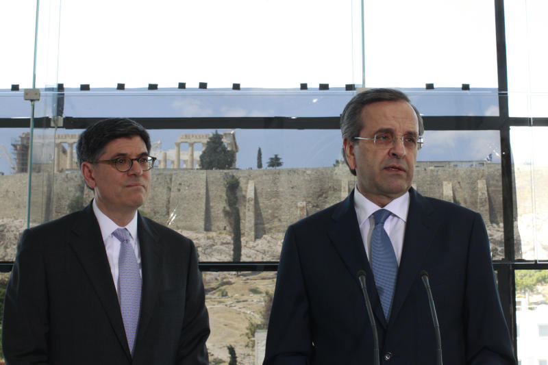 Greek Prime Minister Antonis Samaras, right, speaks to reporters as U.S. Treasury Secretary Jack Lew listens inside the Acropolis Museum in Athens, Sunday, July 21, 2013. U.S. Treasury Secretary Jack Lew arrived in Athens Sunday to discuss Greece's efforts to overcome a deep debt crisis. Samaras is due to visit the United States in early August, where he will meet U.S. President Barack Obama. (AP Photo/Kostas Tsironis, Pool)